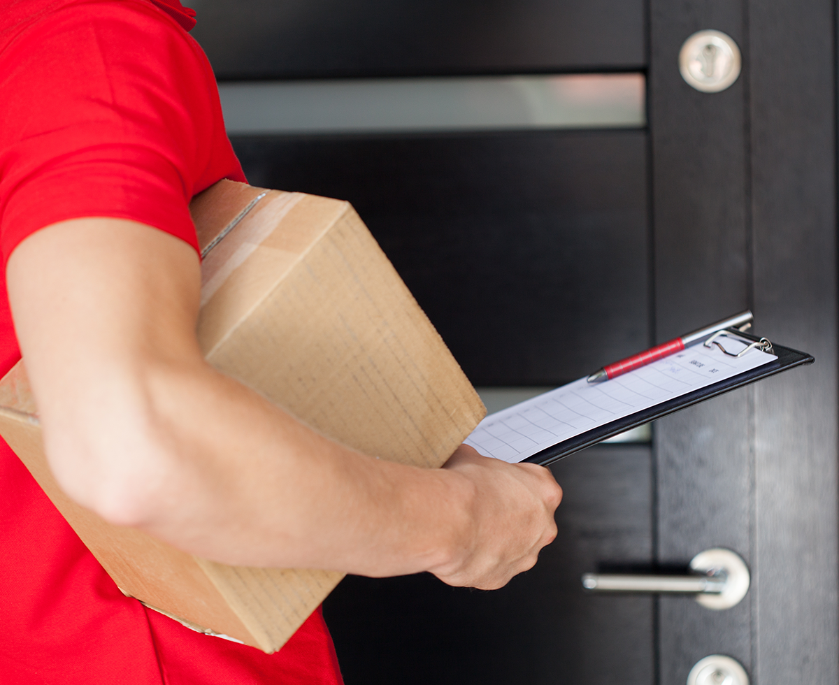 Man at door with package and clipboard